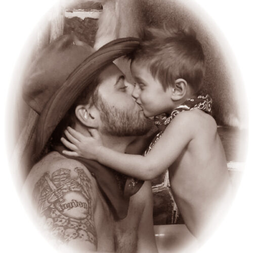 Cowboy Dad Kissing His Son